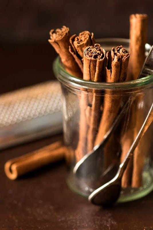Ceylon cinnamon sticks in jar with tongs